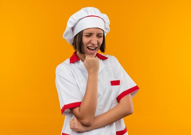 Freudige junge köchin in kochuniform, die faust unter kinn mit geschlossenen augen lokalisiert auf orange setzt