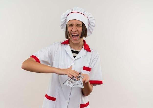Freudige junge köchin in kochuniform, die geld lokalisiert auf weiß hält