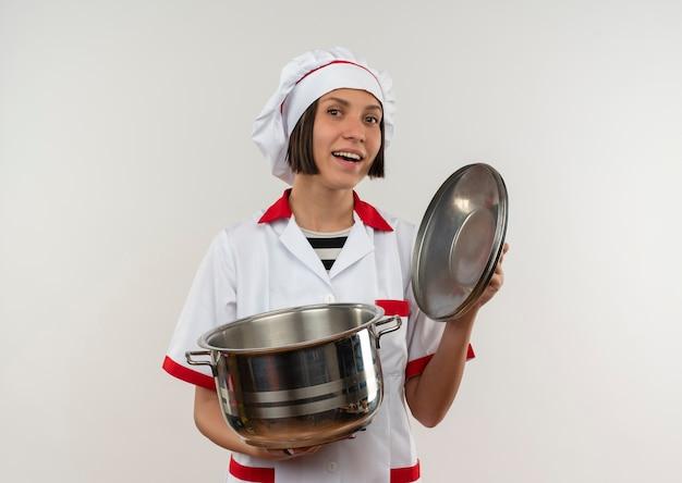 Freudige junge köchin in kochuniform, die topf und topfdeckel lokalisiert auf weiß hält