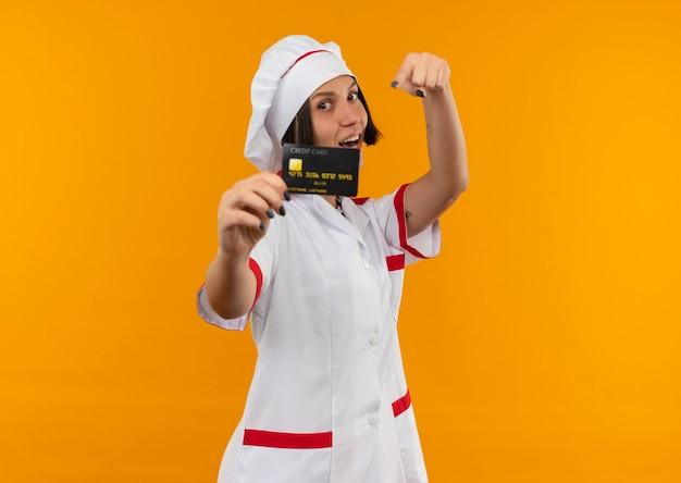 Freudige junge köchin in kochuniform streckt kreditkarte aus und zeigt isoliert auf orange