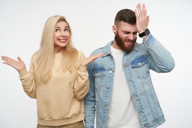 Freudige junge langhaarige blonde frau, die verwirrte handflächen erhebt und breit lächelt, während sie auf weiß mit verwirrtem brünettem hübschem mann im jeansmantel posiert