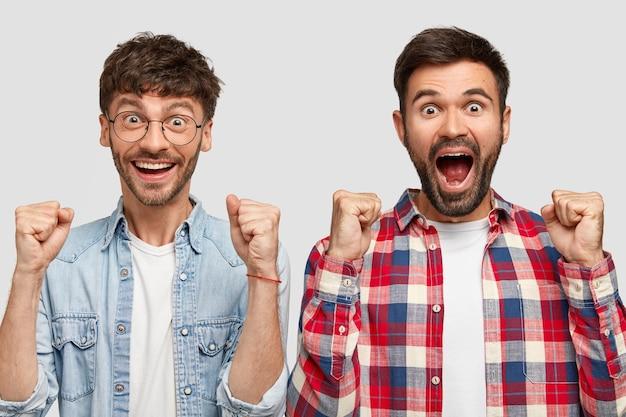 Freudige junge mann gefährten feiern ihren erfolg, schreien und ballten die fäuste, haben überglückliche ausdrücke