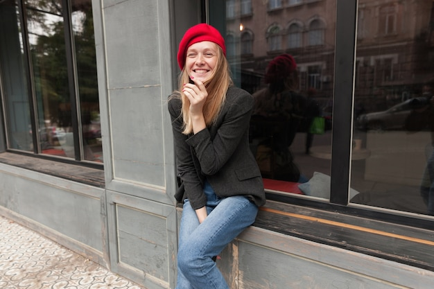 Freudige junge reizende blonde langhaarige frau, die draußen über fensterbank sitzt und hand zu ihrem gesicht hebt, während sie glücklich lacht, gekleidet in elegante kleidung