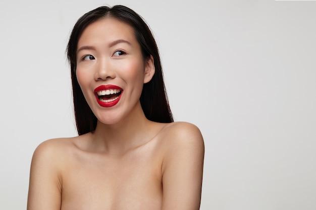 Freudige junge schöne dunkelhaarige dame mit festlichem make-up, das glücklich lächelt, während sie aufgeregt beiseite schaut und hände unten hält, während sie über weißer wand steht