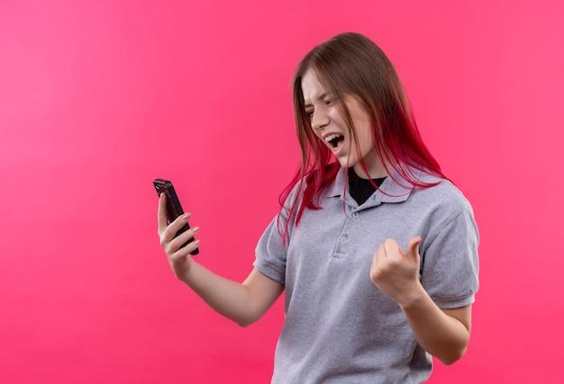 Freudige junge schöne frau, die graues t-shirt trägt, das telefon in ihrer hand betrachtet, die ja geste auf isolierter rosa wand zeigt