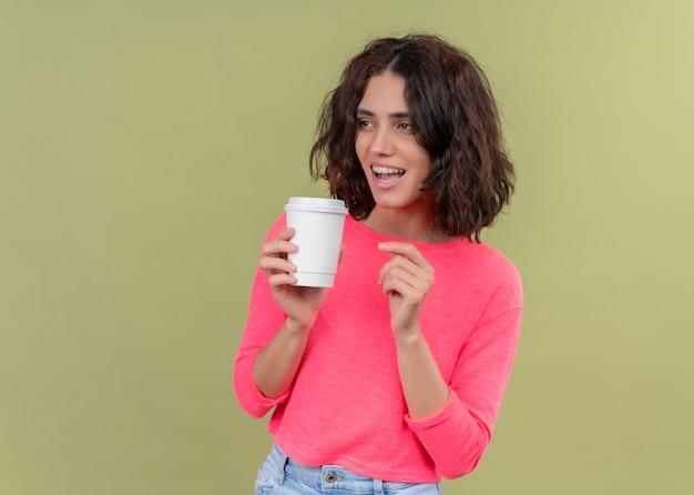 Freudige junge schöne frau, die plastikkaffeetasse hält und linke seite auf isolierter grüner wand mit kopienraum betrachtet