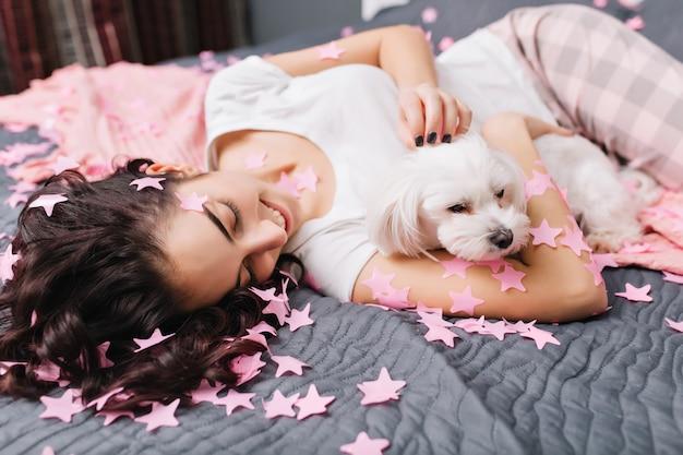 Freudige junge schöne frau mit lockigem brünettem haar im pyjama, das auf bett mit kleinem hund in rosa lametta kühlt. hübsches modell, das zu hause spaß mit haustieren hat und glück ausdrückt