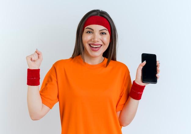 Freudige junge sportliche frau, die stirnband und armbänder hält, die handy suchen, das ja geste tut
