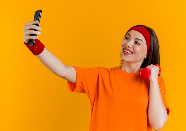 Freudige junge sportliche frau, die stirnband und armbänder hält hantel hält und selfie nimmt