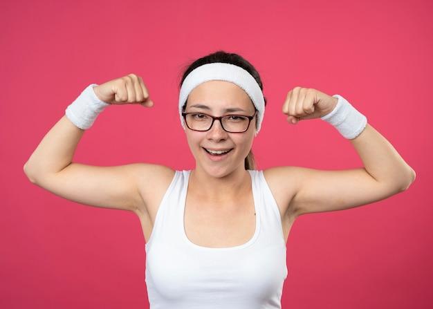 Freudige junge sportliche frau in der optischen brille, die stirnband und armbänder spannt, spannt bizeps lokalisiert auf rosa wand