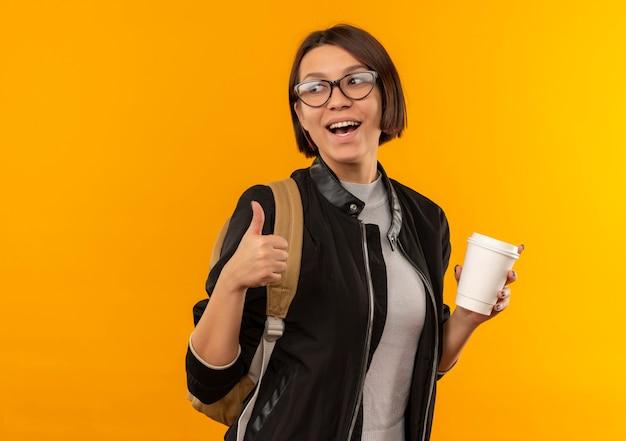 Freudige junge studentin, die brille und rückentasche hält, die plastikkaffeetasse hält, die seite betrachtet und daumen oben auf orange lokalisiert zeigt