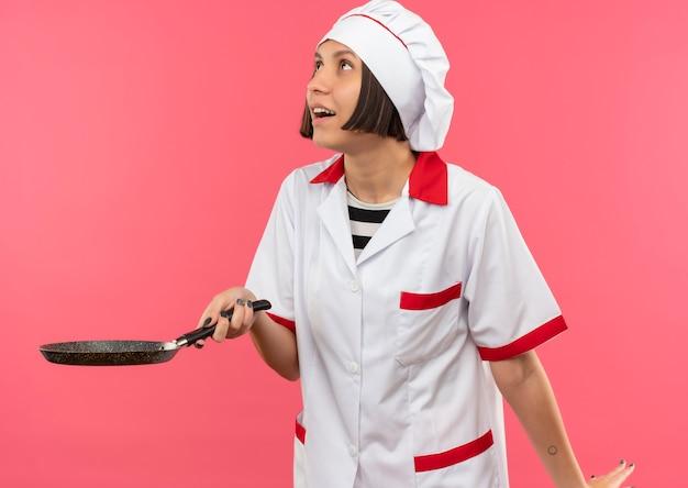 Freudige junge weibliche köchin in der kochuniform, die bratpfanne hält und lokal auf rosa schaut