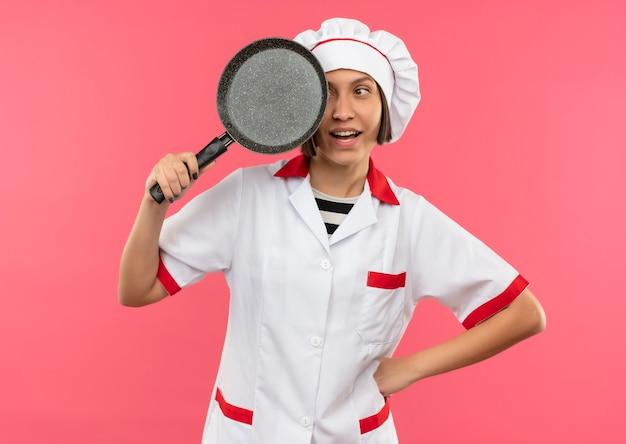 Freudige junge weibliche köchin in der kochuniform, die bratpfanne lokalisiert auf rosa hält