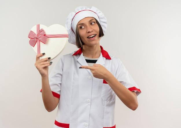 Freudige junge weibliche köchin in der kochuniform, die das schauen und zeigen auf herzförmige geschenkbox lokalisiert auf weiß hält
