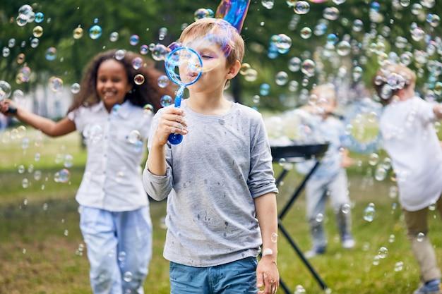 Freudige kinder, die seifenblasen machen