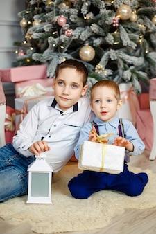 Freudige kinder, die weihnachtsgeschenke öffnen. gemütlicher warmer winterabend. familie am heiligabend. kinder unter weihnachtsbaum mit geschenkboxen. dekoriertes wohnzimmer. nette kinder mit weihnachtsgeschenkboxen zu hause.