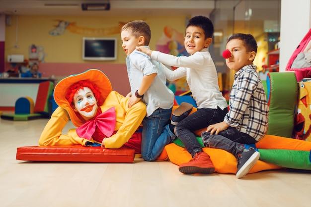 Freudige kleine jungen, die auf lustigem clown im kinderbereich sitzen.