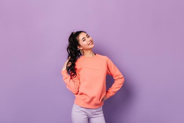 Freudige koreanische frau, die mit hand auf hüfte aufwirft. studioaufnahme der atemberaubenden asiatischen jungen dame, die mit lockigem haar spielt.