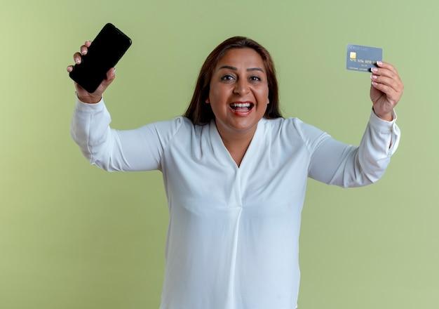 Freudige lässige kaukasische frau mittleren alters, die telefon mit kreditkarte anhebt