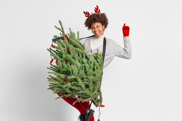 Freudige lockige frau tanzt sorglos hat spaß, bevor das neujahrskonzert einen grünen tannenbaum hält, als ob die gitarre den arm hebt und eine spielerische stimmung hat, glücklich, allein zu hause zu bleiben, trägt rentierhörner. winterferien