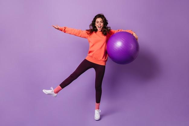 Freudige lockige sportlerin, die spaß im lila studio mit großem fitball hat