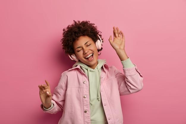 Freudige, lockige teenager-frau tanzt sorglos und hört audiotracks in kopfhörern