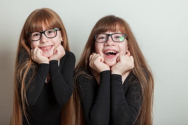 Freudige mädchen in sporttrikots. glückliche schwestern, porträt auf einem weißen hintergrund.