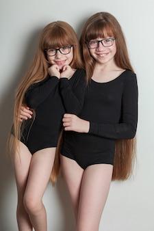 Freudige mädchen in sporttrikots stehen auf einer schwarzen yogamatte mit üppigen pfannkuchen und gesundem haar.