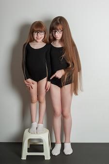 Freudige mädchen in sporttrikots stehen auf einer schwarzen yogamatte mit üppigen pfannkuchen und gesundem haar