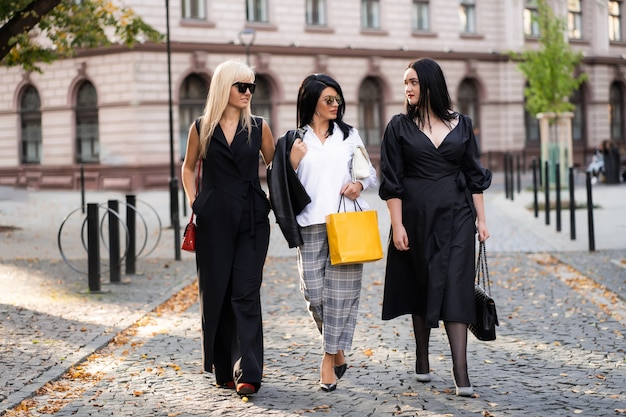 Freudige model-freundinnen, die lächeln, haben nach dem einkauf eine gute zeit. gruppe junger leute, die durch park gehen. freunde, die spaß haben.