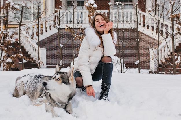 Freudige modische junge frau, die spaß mit husky-hund im schnee auf straße im freien hat. lieben sie haustiere, schöne momente, lächeln sie, drücken sie wahre positive gefühle aus.