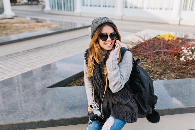 Freudige modische junge frau in warmer winterkleidung, strickmütze, sonnenbrille, die auf straße in der stadt sitzt und am telefon spricht. reisen mit rucksack, kamera, fröhlicher stimmung, positiven emotionen.