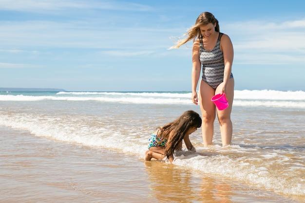 Freudige mutter und kleine tochter, die knöcheltief im meerwasser und im nassen sand stehen und muscheln in eimer pflücken
