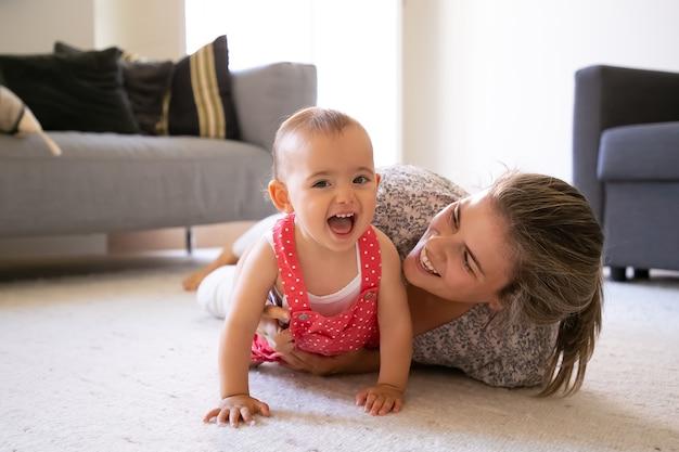 Freudige mutter und kleines mädchen, die auf teppich im wohnzimmer liegen. glückliche blonde mutter, die mit fröhlicher tochter zu hause spielt und lächelt. nettes baby, das mit offenem mund lacht. mutterschafts- und wochenendkonzept