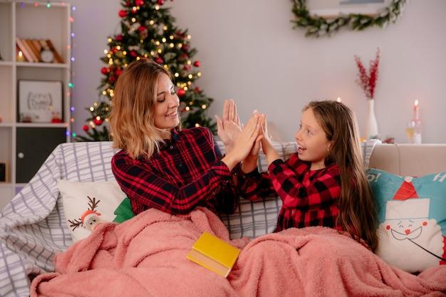 Freudige mutter und tochter spielen und schauen sich bedeckt mit einer decke an, die auf der couch sitzt und die weihnachtszeit zu hause genießt