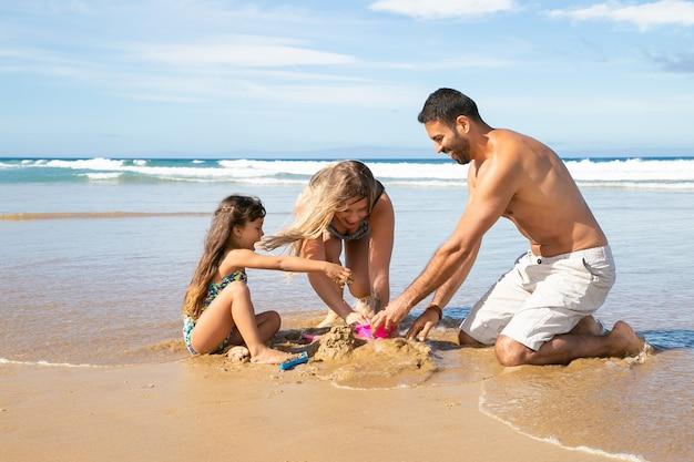 Freudige mutter, vater und kleine tochter genießen gemeinsam urlaub auf see, spielen mit sandspielzeugen der töchter und bauen sandburg