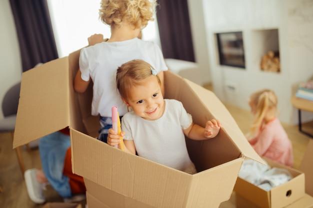 Freudige nette kinder, die zusammen in der box sitzen