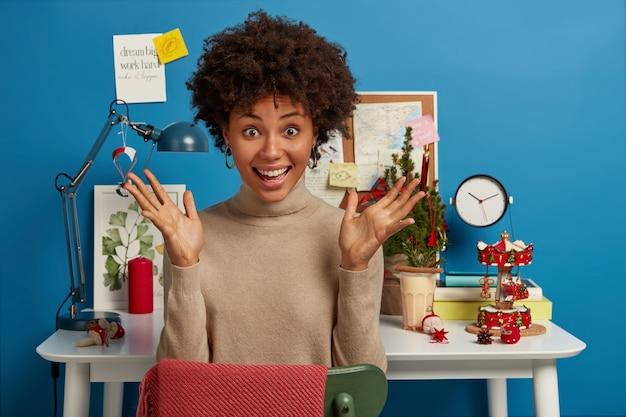 Freudige optimistische dunkelhäutige frau hat beide handflächen angehoben, sitzt auf dem schreibtisch mit weihnachtsbaum und anderen feiertagsattributen