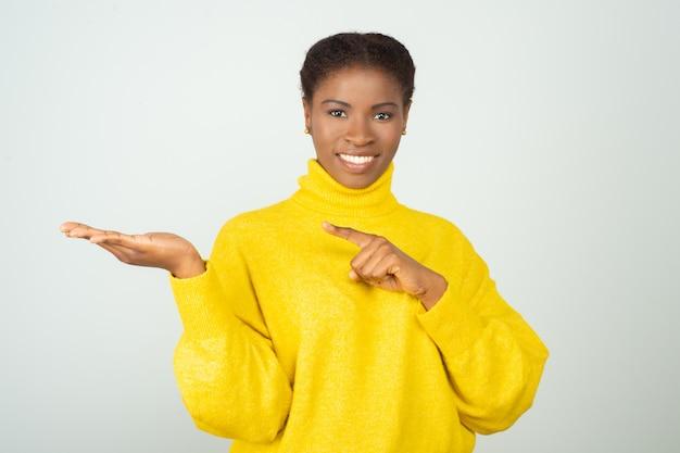 Freudige positive schwarze frau im hellen pullover