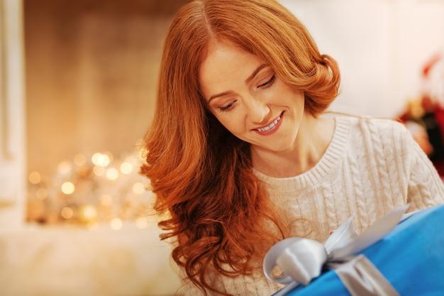 Freudige reife frau, die fröhlich lächelt, während sie seine aufmerksamkeit auf ein geschenk mit schleife richtet und es an einem weihnachtsmorgen öffnet.