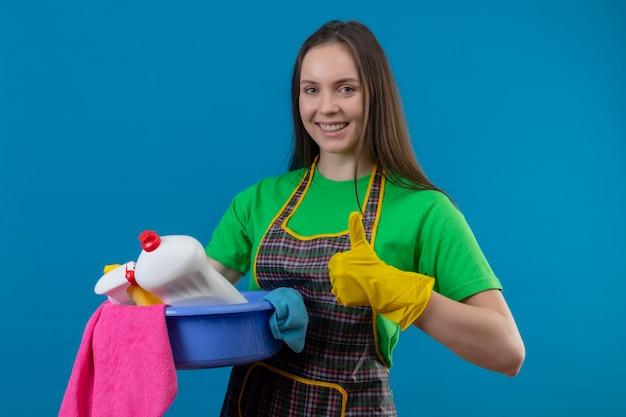 Freudige reinigung der jungen frau, die uniform in handschuhen hält, die reinigungswerkzeuge auf isolierter blauer wand halten