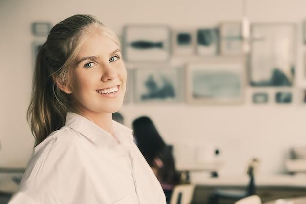Freudige schöne blonde frau, die weißes hemd trägt, im gemeinsamen arbeitsraum steht und sich auf schreibtisch stützt