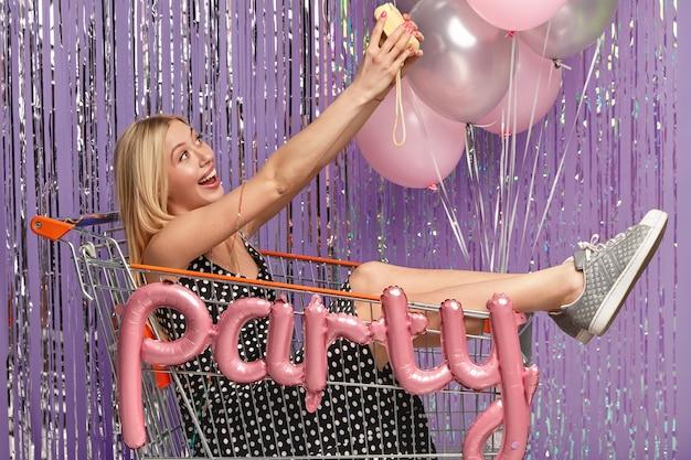 Freudige schöne blonde frau lächelt in die kamera, macht selfie-porträt, posiert im einkaufswagen, in modischen outfit gekleidet, hat spaß auf geburtstagsfeier, dekoriert halle mit luftballons