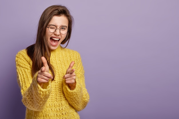 Freudige schöne frau blinzelt mit den augen, ruft vor glück aus, zeigt auf dich, demonstriert ihre wahl Kostenlose Fotos