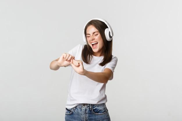 Freudige schöne junge frau tanzt und genießt musik in drahtlosen kopfhörern.