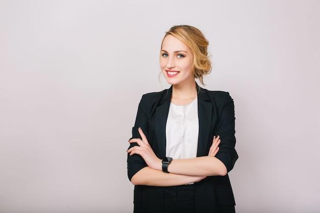 Freudige selbstbewusste blonde geschäftsfrau im anzug, die isoliert lächelt. moderner arbeiter, sekretär, manager, erfolgreiche, fröhliche stimmung.