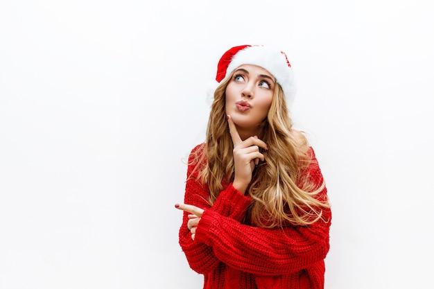 Freudige sorglose blonde frau im neujahrshut im roten strickpullover, der auf weißer wand aufwirft. isolieren. weihnachts- und neujahrsparty-konzept.