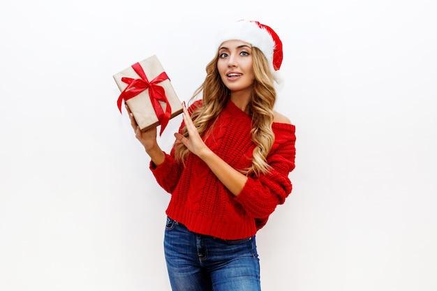Freudige sorglose blonde frau in niedlichen maskeradegläsern und neujahrshut im roten strickpullover, der auf weißer wand aufwirft. isolieren. weihnachts- und neujahrsparty-konzept.