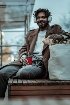 Freudige stimmung. freundlicher internationaler mann, der lächeln während seiner snackpause auf seinem gesicht hält