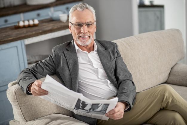 Freudige stimmung. positiv entzückter mann, der beine kreuzt, während auf seinem sofa sitzt und vor der kamera lächelt